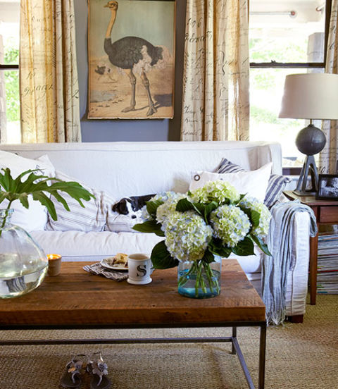 "The neutral palette of this North Carolina house is enlivened by mixing in a variety of textures—the coffee table's reclaimed wood, a nubby sea-grass rug, and a steel lamp base forged from a car jack. Design Legacy linen curtains, printed with an antique script, and striped pillows introduce subtle hints of pattern. ""I wanted a living room that felt calming, not boring,"" says the owner, an interiors stylist."