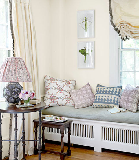 In the living room of this New York farmhouse, John Robshaw throw pillows help cushion a radiator-obscuring bench. The insect photos, by Linda B. Horn, hang on a wall painted White Dove by Benjamin Moore.