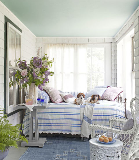 """Minnie (left) and Nash get cozy on the porch's iron-and-brass daybed, sporting a vintage seersucker coverlet. The Moroccan rug is from Canvas. """"It's my happy spot,"""" Kurgan says of her front porch. """"In the afternoon, when the light is coming in, it's one of my favorite places in the whole world."""""""