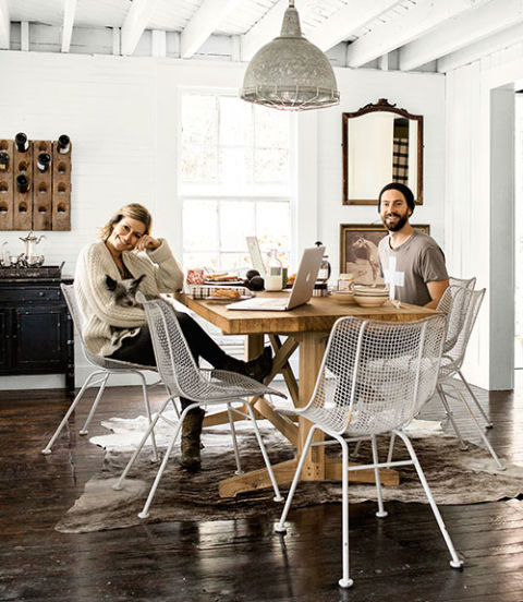 The owners of this Pennsylvania home, with their terrier, Tom, relax in midcentury Woodard chairs. A friend crafted the dining table out of wood salvaged from a bowling lane. The oversize light formerly illuminated a factory. The walls are painted High-Gloss White by Behr.