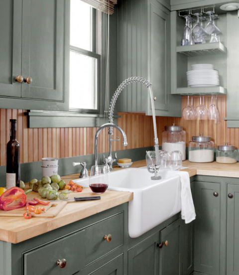 Most folks opt for white in the kitchen, but this Montana farmhouse's kitchen is bathed in moodier hues. The custom cabinets are painted in Benjamin Moore's Mohegan Sage while the fir beadboard is a golden brown—giving the 75-square-foot spot a jewel box feel. An ivory apron-front sink by Shaws offers a burst of brightness.
