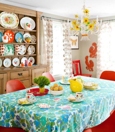 The dining room of this colorful Maine home features plastic Eames-look-alike chairs that were found on Craigslist for $25 each. A Goodwill plate mingles with other secondhand dishware on the early-19th-century pine hutch.