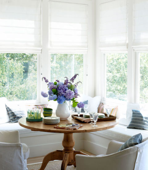To create a dining nook, the homeowner of this California farmhouse pulled up a pine pedestal table and slipcovered armchairs to built-in benches. An ironstone jug holds a mix of hydrangeas and lilacs.
