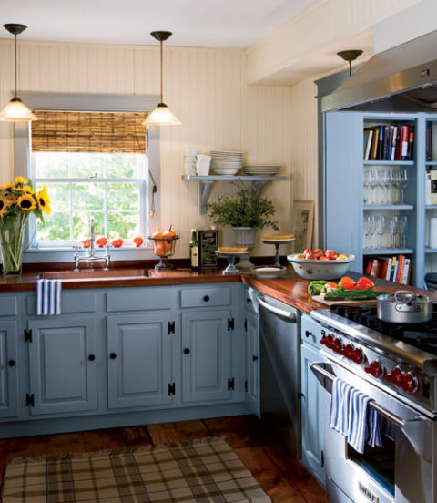 A mix of old and new warms this Sag Harbor cottage's country kitchen, with mahogany countertops, stainless-steel appliances, and the dusty blue cabinets. Creamy beadboard walls and open shelves keep the room light.