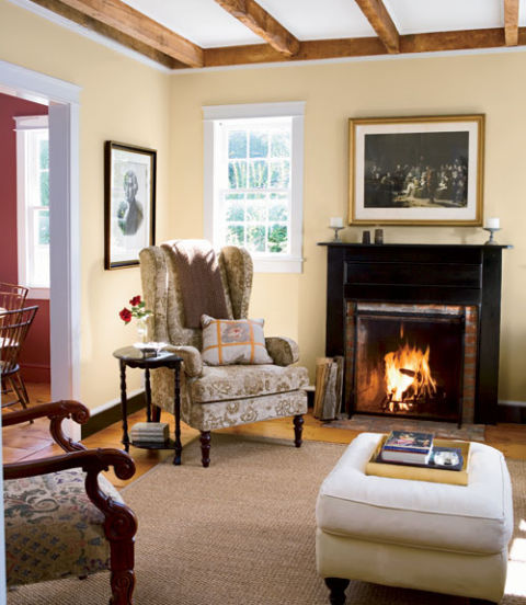 Richard and Bob opened up the kitchen to a new family room addition with a sloping 11-foot ceiling, and Richard opted to add a few modern amenities such as air-conditioning and a pool. In this photo: The duo painted the early fireplace mantel black to add a jolt of color to the neutral room.  RELATED: 101 Living Rooms You'll Love