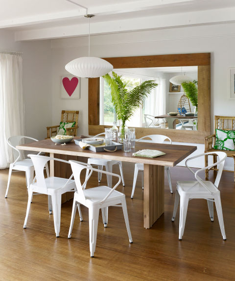 Steel bistro chairs, ordered from overstock.com, surround a white oak table from Crate & Barrel in the dining room of this New York home.<br />