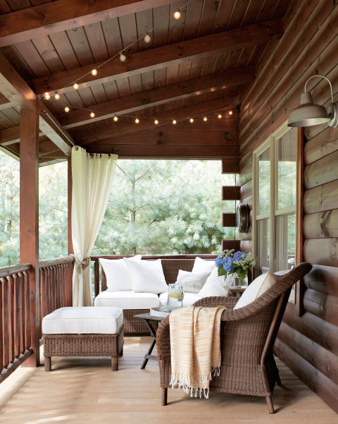 String lights from Target twinkle over the front porch of this Ohio lake house, and Pottery Barn wicker furniture surrounds an antique folding table, where the family plays cards.