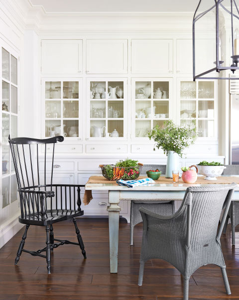 This California farmhouse kitchen built-ins hold all her ironstone and glassware. The Windsor chair is by Ethan Allen; the wicker seats are Janus et Cie. White Dove by Benjamin Moore covers the walls.<br />