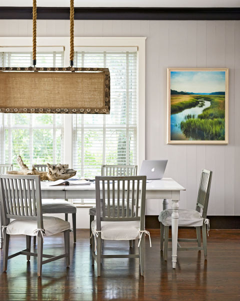 The dining-room fixture in this South Carolina home was fashioned from reclaimed oyster sticks (used to farm the mollusks), and the farmhouse table and chairs are by Shabby Chic. The owner shot the photo in a marsh on the property. The walls are painted Cedar Key by Benjamin Moore.<br />