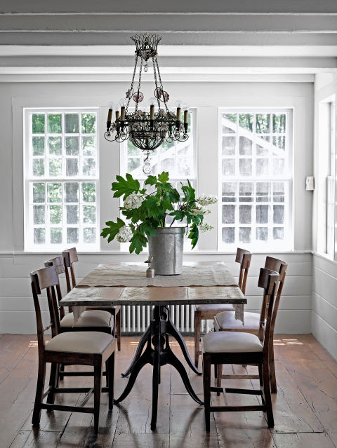 The ornate light fixture in this Connecticut farmhouse from a Paris flea market offsets the simplicty of the owner's antique farm table and chairs.<br />