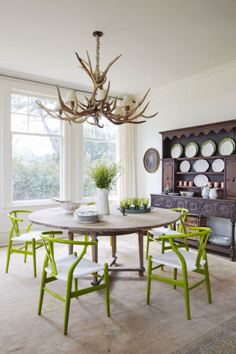 Inspired by the lush landscape just outside the enormous windows (which were salvaged from an old train depot!), Bailey filled the room with rustic wood elements and pops of green. The previous owners left behind the giant antler chandelier, which suited Bailey just fine. From there, she selected an antique round table that she had stripped down to the raw wood for a more worn and weathered look. Beech wishbone chairs, which Bailey had lacquered in an apple green shade, make for a lively juxtaposition with the table. They also pop against the large antique hutch that stores her collection of copper Moscow mule mugs and green and white china. A pale pink Oriental rug with subtle hints of sky blue and chartreuse rounds out the mix.