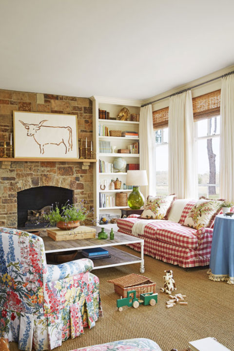 "Bailey designed this space to be roomy enough to host a crowd but cozy enough for family game nights around the fire. ""I wanted a few big pieces of indestructible furniture that people could pile on, plus some modern elements so it didn't feel too 'themey,' "" says Bailey. Case in point: Bailey paired the room's showstopping farmhouse icons—a buffalo check-covered sofa and wildflower chintz armchair—with a streamlined steel-framed coffee table and graphic longhorn watercolor painting (by Houston artist Mary H. Case) to keep the mix from going too traditional. Bright idea: When weekend guests ask, ""What can I bring?"" Bailey suggests a beloved paperback book with an inscription to add to their library."