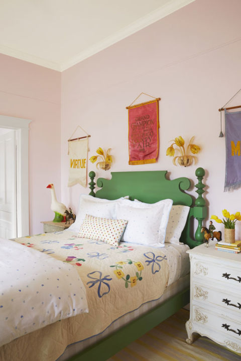 "Bailey embraced her love of pink and green full tilt by painting the walls of her daughter Grace's room a soft shade of the former and choosing a traditional country bed frame in a leafy shade of the latter. An antique quilt looks surprisingly modern when paired with graphic heart-print bedding (from Biscuit, and appropriately named ""Grace""). Vintage finds, like the Murano glass tulip sconces and the fair banners hanging above thebed (a Round Top find, and Bailey's first purchase for the house) infuse the space with personality."