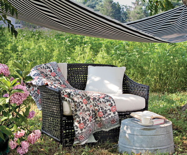 faux wicker love seat with quilt under an awning