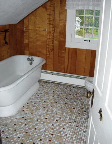 Bathroom With Wood Paneled Walls And Sloping Ceiling