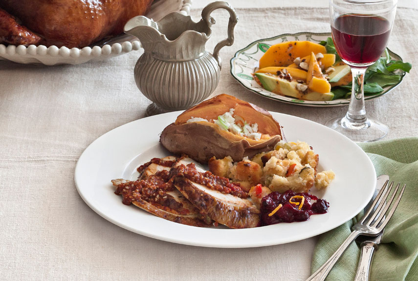 turkey with thanksgiving side dishes, like cornbread stuffing, roasted sweet potatoes, and avocado-papaya salad