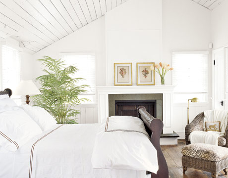 all white bedroom with sleigh bed and plant
