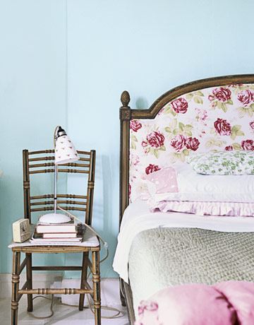 chair with a floral lamp beside a floral bed