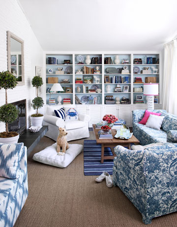 "What a difference! Covering the overpowering yellow hue with crisp white created a serene backdrop, plus the illusion of more space.  ""Provide visual interest by arranging some books horizontally,"" says Eddie Ross. ""You can also place accessories atop the stacks."" Coating the built-in unit's interior with a pale blue added depth."
