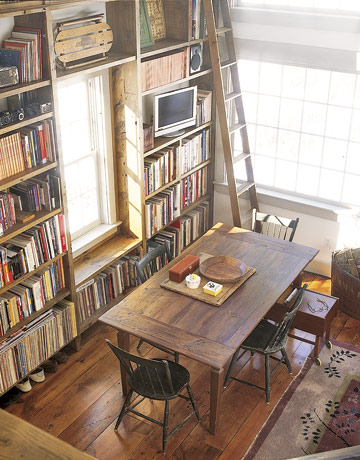A floor-to-ceiling bookcase in the barn holds a collection of vintage children's books on this farm with storybook charm.