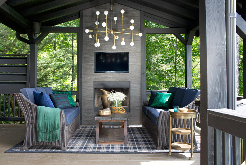 The fireplace in this Georgia log cabin was covered in inexpensive porcelain tile. The brass chandelier finishes the space with a little sparkle.