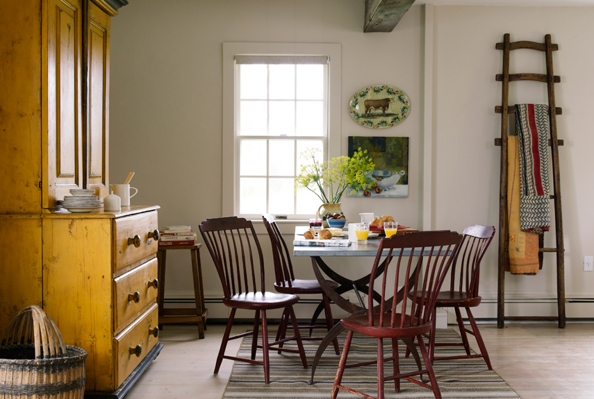 An early-American hutch and an English apple-picking ladder create bold accent colors in the dining room of this quaint Connecticut cottage.<br />