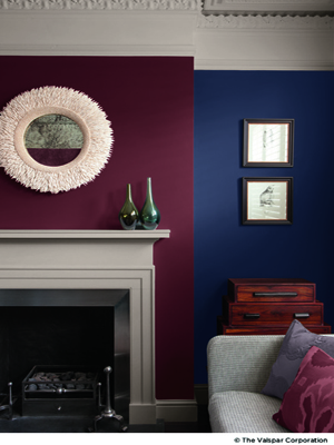 purple and red living room with white mantel and stacked suitcases