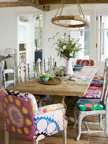In the dining room of this Martha's Vineyard home, Suzani fabric covers silver-painted wood seats by Redford House and Zentique's armchairs and birch sidechairs. The pine dining table is from Restoration Hardware.<br /> Bright idea: Unify different dining chairs with cohesive upholstery.<br />