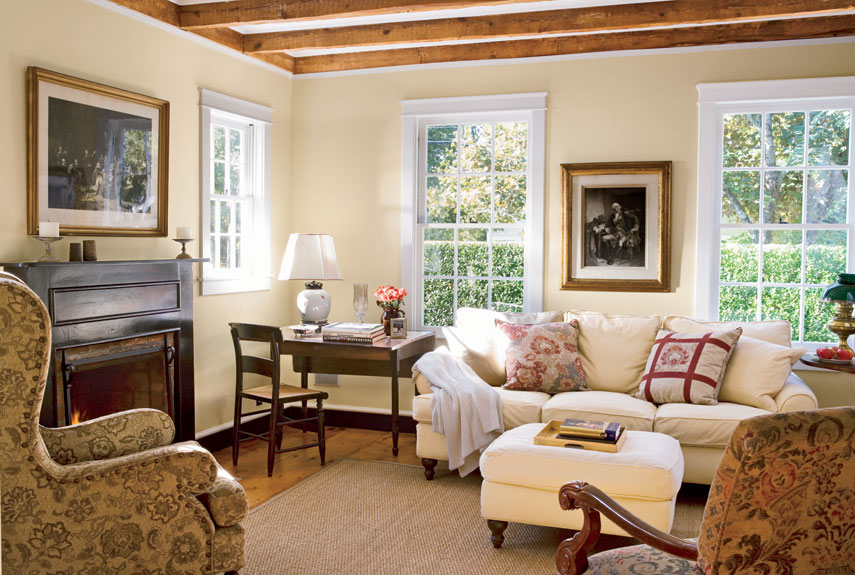 """The beauty of the floors and beams are 200 years' worth of nicks and crannies, warping, weathering, and nail holes. They look beautiful just as they are,"" says Richard.  In this photo: The buttercream-colored living room boasts original windows."