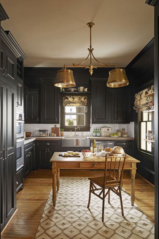 "The previous owners had restored the 105-year-old home, so the kitchen didn't need a total gut job. What it did need were some simple but substantial cosmetic upgrades—starting with paint. When the McCarthys moved in, the walls were beige and the cabinets, which vary in height, were white. ""Painting everything black seemed like a good way to make the cabinets blend in with the wall,"" says Bailey. Next, she swapped out the granite countertops for butcher-block ones. ""We wanted the feeling of an old farmhouse that would age nicely with us,"" she says. ""Butcher block is practical, casual, and the opposite of trendy."""