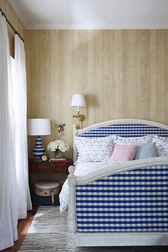 "Bailey designed the room, which was originally the house's parlor, around her company's Wimberley pattern (named after the small Texas town known for its beautiful wildflowers). She upholstered the white-painted bed in a graphic blue-and-white-check fabric to complement the whimsical sheets. Wallpaper with a wood grain pattern, a fresh way to achieve a similar effect as unpainted, wood-paneled walls, creates a warm backdrop for the crisp bed. Gauzy eyelet curtains finish the space with a dose of pretty. ""They add a country touch without going full-on 'granny,' "" says Bailey. Bright idea: A sconce provides enough light for Bailey's late-night reading habit without disturbing her husband."