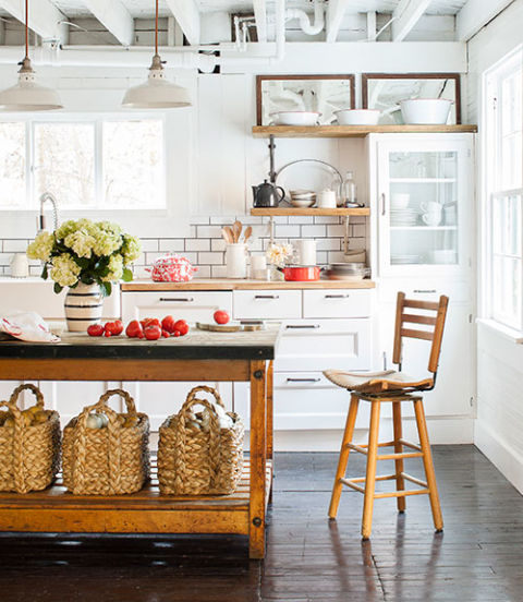 An antique bakery table, equipped with Pottery Barn baskets, functions as the kitchen island in this Pennsylvania home.
