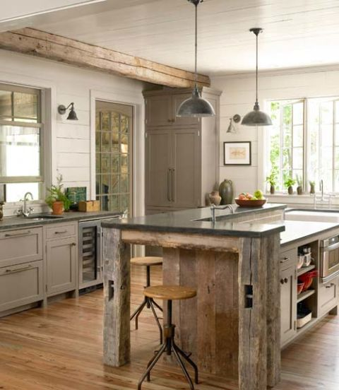 A custom island, topped with sheet metal, echoes this Georgia home's barnwood beams. Why stop at the usual overheads? Additional sconces make any countertop an enlightened place for prep work.