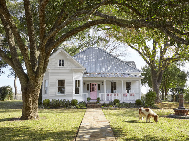 "You'd never guess Bailey McCarthy had an urban upbringing by the look of her Bellville, Texas, country home. Filled to the brim with buffalo checks, antique quilts, and fair memorabilia, the century-old Victorian farmhouse is an homage to iconic country decor. ""I've lived in a lot of cities, but I've always been more of a country mouse,"" she says. The interior designer, owner of Biscuit (a bedding line and housewares boutique in Houston) and author of the popular blog Peppermint Bliss, attributes her soft spot for pastoral life to childhood summers spent at her grandfather's ranch in Brookshire, Texas. She wanted her own children to have a similar experience, so when she and husband Pete happened upon a charming farmhouse on 85 acres, they snatched it up. Here's how she embraced her downhome roots to give this farmhouse a fresh—and timeless—look. In this photo: Solider Boy, the family's 2-year-old Shetland pony, poses in front of the house."