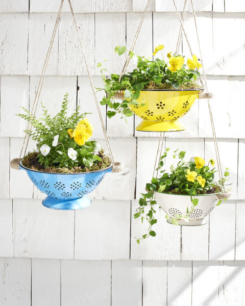 Hang spring flowers in brightly colored colanders for an unexpected and truly unique way to update your porch. Get the full tutorial.