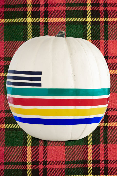 No carving required? Now that's an idea we can cozy up to! Start with a white pumpkin, such as a lumina (or paint a regular pumpkin a matte white). Wrap electrical tape in green, red, yellow, and blue ($9 for assorted pack of six; amazon.com) around the pumpkin, taking care to make sure all lines are evenly spaced and that all seams meet in the same area. For black lines, cut 5-inch-long pieces of electrical tape in half and apply to pumpkin as shown.