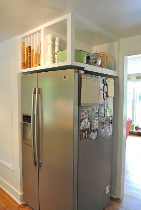 Here, an awkward corner refrigerator becomes super handy with built-in overhead shelving. An open area holds large items like a slow cooker, while  slotted sections keep cookie sheets and cutting boards in place. See more at Bev Cooks »