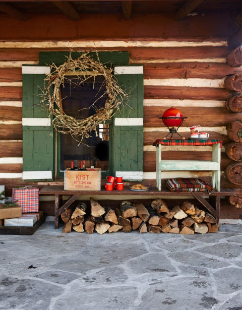 Made of moss- and lichen-covered twigs, the wreath sets an unfussy tone for visitors. Mulled wine, served from a 1960s Danish muller (right) adds to the warm welcome of this cozy cabin.