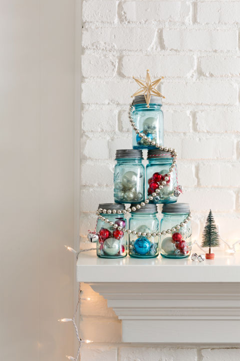 This idea's perfect for a mantel or entry table: Fill six like-sized canning jars with ornaments, tinsel, greenery, you name it. Assemble the jars in a pyramid, then wrap it with a shiny garland and top with a star. Done!