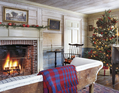 den with christmas tree and antique settee in front of a fireplace