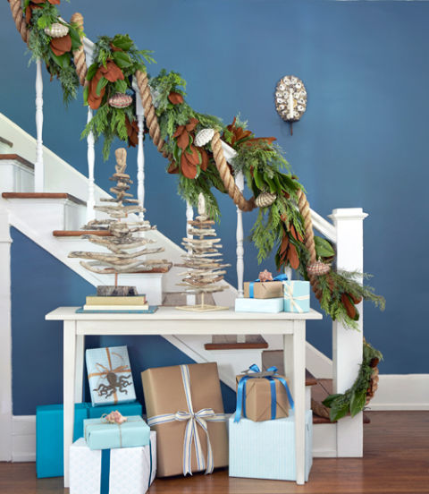 Salvaged tabletop driftwood trees, discarded shells affixed to a mirrored, candlelit sconce, and a nautical garland add festive touches to this this easy-breezy stairwell.