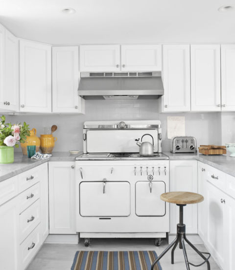 The homeowner kept the kitchen's old Chambers stove and cabinets—now improved with new fronts and a coat of Benjamin Moore's Patriotic White—but jettisoned the Formica counters and dark backsplash in favor of marble and white subway tiles. A Design Workshop stool from ABC Carpet & Home and a Dash & Albert rug decorate the kitchen.