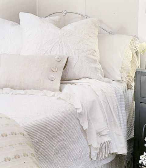 An all-white bed makes mixing patterns and textures easy. This bed boasts at least four different textiles in different shades of white, including lace, matelasse and homespun fabrics.<br /><br /><br />