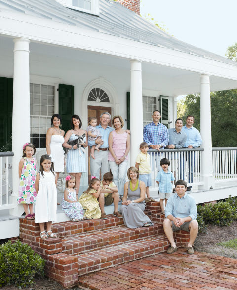 Mac and Tere Thomas join their family on the front porch. Top row, from left: daughters-in-law Summer and Nicole, Mac (holding granddaughter Khloe), Tere, son Barrett, son-in-law Eric Haik, and son William. Bottom row, from left: grandchildren Katelyn, Londyn, Anna-Claire, Maria, and William IV; daughter Erin Haik; grandsons Bennett and Thomas; and son Grant.