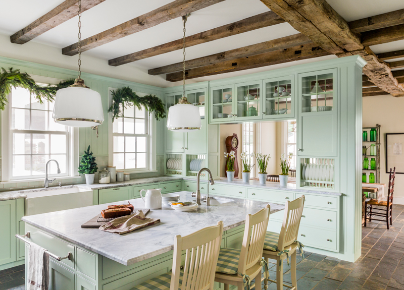 modern farm kitchen with mint green walls and stone counter island with seating