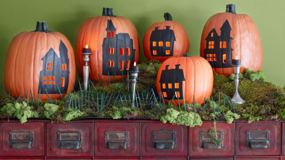 A passel of pumpkins provides the backdrop for a quaint village scene. Step 1: Carve a hole in the bottom of each pumpkin, scoop out the pulp, and return the cut pieces. Step 2: Print out these house templates. Resize on a copier, scaling the images to fit your pumpkins. Step 3: Cut out stencils as directed on the templates and affix to pumpkins with masking tape. Trace on the designs with a felt-tip pen. Step 4: Remove stencils, then carefully carve along the drawn lines of the houses' windows with an X-Acto knife. Fill in the designs using a fine-tip brush and black flat acrylic paint; let dry. Affix a battery-operated votive candle in the base of each pumpkin with adhesive putty.